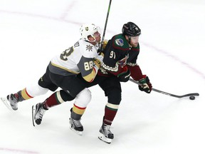 Nate Schmidt (88) of the Vegas Golden Knights hits Taylor Hall (91) of the Arizona Coyotes during an exhibition game prior to the 2020 NHL Stanley Cup Playoffs at Rogers Place on July 30, 2020.