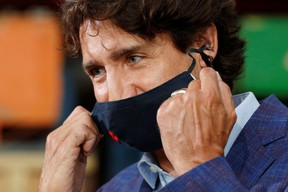Canada's Prime Minister Justin Trudeau removes his face mask before speaking at the 3M's plant in Brockville, Ont. on Friday, Aug. 21, 2020.