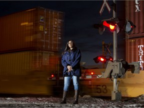 Maple Crest resident Christina Jarvis poses for a photo as a train passes in the background, in Edmonton Friday Jan. 15, 2021. Jarvis is concerned that a train crossing at the one entrance and exit to the neighbourhood can block emergency crews. Photo by David Bloom