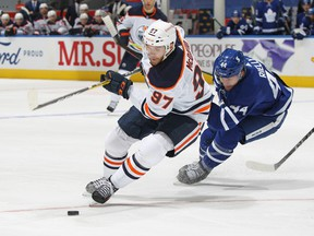 Connor McDavid (97) of the Edmonton Oilers swings around Morgan Rielly (44 )of the Toronto Maple Leafs at Scotiabank Arena on Jan. 22, 2021. The Maple Leafs defeated the Oilers 4-2.