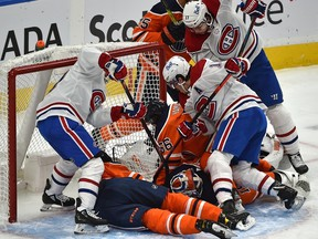 Montreal Canadiens players crowd the Edmonton Oilers crease trying to jam the puck past goalie Mikko Koskinen (19) at Rogers Place in Edmonton on Jan. 18, 2021.