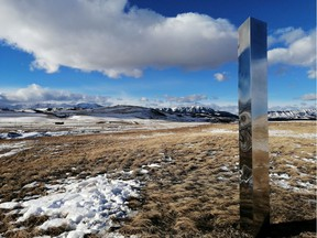 A monolith in Alberta is shown in a recent handout photo. A tall, stainless steel beacon that has been placed along the eastern slopes of the Alberta Rockies comes with a message.  The three-metre monolith, which reflects its surroundings, is one of many that have been found at sites around the world. They have been found on a California trail, a Utah desert and in Romania.