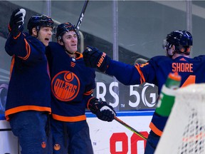 Edmonton Oilers' Alex Chiasson (39) celebrates a goal with Kyle Turris (8) and Devin Shore (14) on Winnipeg Jets' goaltender Connor Hellebuyck (37) during first period NHL action at Rogers Place in Edmonton, on Monday, Feb. 15, 2021.