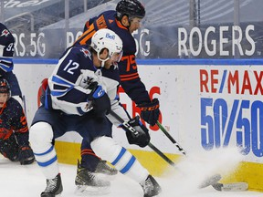 Winnipeg Jets forward Jansen Harkins (12) and Edmonton Oilers defensemen Evan Bouchard (75) battle for loose puck during the second period at Rogers Place on Feb. 15, 2021.