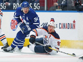 Connor McDavid (97) of the Edmonton Oilers battles for the puck against Auston Matthews (34) of the Toronto Maple Leafs during the first period an NHL game at Scotiabank Arena on March 29, 2021 in Toronto.