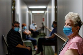 Residents wait outside of their rooms for nurses from Humber River Hospital to administer the Pfizer/BioNTech COVID-19 vaccine at Caboto Terrace, an independent seniors residence.