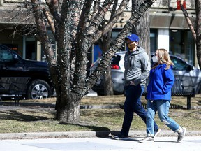 Masked pedestrians are seen walking along 17 Ave S.W. on Friday, April 2, 2021.