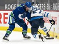 J.T. Miller (9) of the Vancouver Canucks battles with Nikolaj Ehlers (27) of the Winnipeg Jets for control of the puck at Rogers Arena in Vancouver on March 22, 2021.
