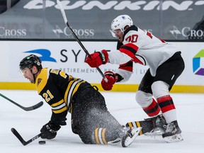 New Jersey Devils defenseman Dmitry Kulikov (70) checks Boston Bruins left wing Nick Ritchie (21) during the first period at TD Garden on March 30, 2021.