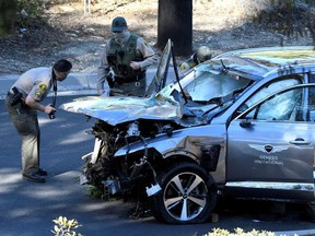 Los Angeles County Sheriff's Deputies inspect the vehicle of golfer Tiger Woods, who was rushed to hospital after suffering multiple injuries, after it was involved in a single-vehicle accident in Los Angeles, California, U.S. February 23, 2021.