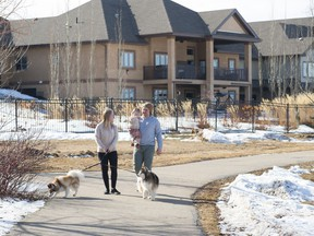 Chelsea and Josh Philpott take a walk with their daughter, Sophie, and dogs Hulk, left, and Leslie, in their new community of Genesis on the Lakes in Stony Plain.