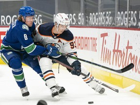 Brock Boeser (No. 6) of the Vancouver Canucks attempts to check Ryan Nugent-Hopkins (No. 93) of the Edmonton Oilers away from the puck during the first period at Rogers Arena on May 3, 2021 in Vancouver.