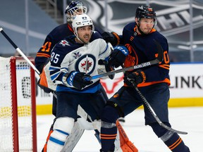 Edmonton Oilers' Dmitry Kulikov (70) battles Winnipeg Jets' Mathieu Perreault (85) during the second period of NHL North Division playoff action at Rogers Place in Edmonton, on Wednesday, May 19, 2021.