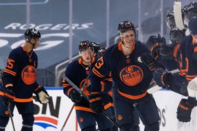 Edmonton Oilers' Jesse Puljujarvi (13) celebrates his goal on Winnipeg Jets' goaltender Connor Hellebuyck (37) with teammates during the second period of NHL North Division playoff action at Rogers Place in Edmonton, on Wednesday, May 19, 2021.