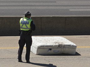 Police continue to investigate at the scene after a single vehicle collision on the west bound Whitemud Drive between 66 Street and 91 Street, in Edmonton Saturday June 12, 2021. Initial social media reports suggested that a person on a motorcycle had been hit by a mattress. Photo by David Bloom