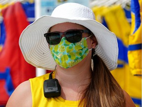 Lifeguard Eliza Rasmussen follows pandemic health restrictions by wearing a face mask at Queen Elizabeth Outdoor Pool in Edmonton on Monday, June 14, 2021, when the pool opened to the public.