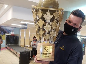 Edmonton Stingers president Brett Fraser arrives at the Edmonton International Airport on Aug. 10 with the Canadian Elite Basketball League championship trophy in hand after the club won the Summer Series in St. Catharines, Ont.