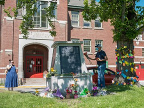 People lay flowers in front of the administration building at the former Kamloops Indian Residential School, after the remains of 215 children were found at the site in Kamloops, B.C., May 29, 2021.