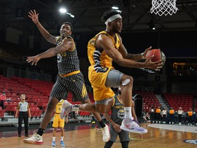 Edmonton Stingers guard Mathieu Kamba (right) evades a block from Hamilton Honey Badgers forward Kalif Young during Canadian Elite Basketball League game action at the Edmonton Expo Centre on Saturday June 26, 2021.