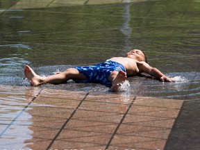 Ibrahim Khussanov ,5, tries to stay cool in the fountain in front of City Hall as temperatures rose to 29 C on Tuesday, June 22, 2021 in Edmonton.