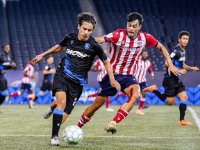 Paris Gee of FC Edmonton, left, plays the ball away from Rafael Nuñez Mata of Atlético Ottawa in a CPL contest at Investors Group Field in Winnipeg on July 18, 2021.
