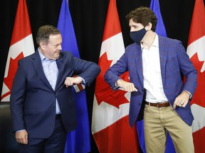 Prime Minister Justin Trudeau bumps elbows with Alberta Premier Jason Kenney after a meeting in Calgary on July 7, 2021.