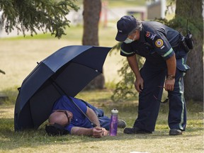 Emergency medical personnel speaks with a man who seemed to have suffered heat stroke at the Edmonton Heritage Festival held at Hawrelak Park in Edmonton on Saturday July 31, 2021. A heat wave has descended upon the Edmonton region with high temperatures climbing to 33C degrees in the city.