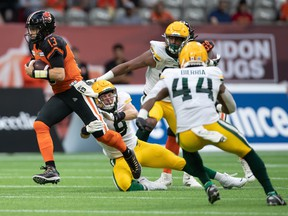 B.C. Lions quarterback Michael Reilly (13) gets away from Edmonton Elks defensive end Mathieu Betts (9) and rushes for a first down in Vancouver on Thursday, Aug. 19, 2021.