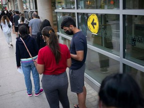 Voters are pictured on Sept. 20, 2021 as they line up at the Toroto Reference Library to cast ballots in Canada's federal election.