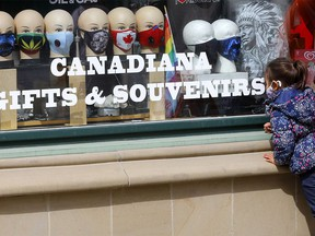 A small child looks over masks at a storefront on Stephen Avenue mall in downtown Calgary as COVID cases continue to rise on Monday, May 3, 2021.