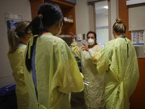 Nurses get ready before going into assist a COVID-19 patient on the ICU at Peter Lougheed in Calgary on November 14, 2020.