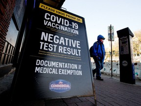 A pedestrian, wearing a face mask to protect against COVID-19, makes their way past a sign advertising the COVID-19 restrictions in place outside the Commercial Hotel-Blues On Whyte Pub on Thursday Oct. 7, 2021.