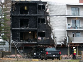 A security guard at the scene of a fire at 8630 106 Ave. in Edmonton on Saturday, Oct. 23, 2021.
