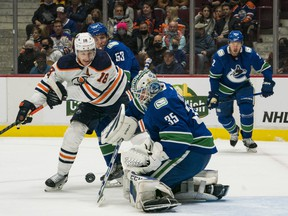 Vancouver Canucks goalie Thatcher Demko (35) makes a save as forward Bo Horvat (53) checks Edmonton Oilers forward Zach Hyman (18) at Rogers Arena on Oct 9, 2021.