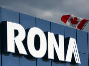 A Canadian flag flies over Rona Inc. signage displayed at the company's store in Toronto.