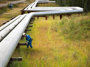 A man works next to pipelines at Cenovus Energy's Foster Creek plant.