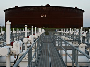 A manifold system, used to direct oil around the facility, stands near crude oil storage tanks in Cushing, Okla.