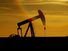 An oil well pumps against the setting sun