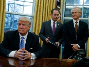 National Trade Council adviser Peter Navarro, right, and White House Chief of Staff Reince Priebus, center, await President Donald Trump's signing three executive orders