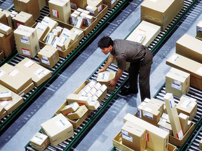 A driver sorts packages in the hub at a United Parcel Service facility. A study has found that Canada Customs in more likely to collect taxes and duties on parcels imported via a service like UPS than parcels sent through the mail system.