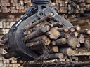Workers pile logs at a softwood lumber sawmill in Saguenay, Que.