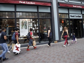 In this Friday, Aug. 25, 2017, photo, shoppers walk past a Foot Locker store in Boston. On Tuesday, Aug. 29, 2017, the Conference Board releases its July index on U.S. consumer confidence. (AP Photo/Charles Krupa)