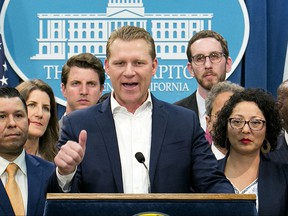 FILE -- In this Monday, July 17, 2017 file photo, Assembly Republican Leader Chad Mayes, R-Yucca Valley, center, discusses the cap-and-trade bill at the Capitol in Sacramento, Calif. Mayes who joined with six of his GOP colleagues in voting for the recent cap-and-trade bill, received $15,300 from the oil industry during the first half of 2017.(AP Photo/Rich Pedroncelli, file)