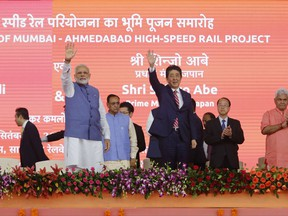 Japanese Prime Minister Shinzo Abe, right and Indian Prime Minister Narendra Modi wave during the ground breaking ceremony for high speed rail project in Ahmadabad, India, Thursday, Sept. 14, 2017. (AP Photo/Ajit Solanki)