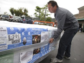 FILE - In this Feb. 27, 2012, file photo, Chris Kraft loads a new mattress set that he purchased at Costco Wholesale store in Glendale, Calif. Shopping for a new mattress has never been easier, or more complicated. The variety of mattress options can be confusing even before you try to sift through the jargon soup of components and materials touted by manufacturers as the leading edge of comfort.  (AP Photo/Damian Dovarganes, File)