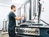 A Microsoft employee loads a slate of magnesium into a water-jet cutting machine for a hardware prototype.