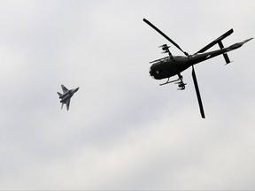 FILE - In this Feb. 13, 2010 file photo, a Serbian army Gazelle helicopter flies as a MiG 29 fighter pass overhead during exercise at a ceremony marking Statehood Day and Army Day, in Belgrade, Serbia. Russia has started the delivery of six MiG-29 fighter jets to Serbia in what could worsen tensions with neighboring states and trigger an arms race in the war-weary Balkan region. (AP Photo/Darko Vojinovic, File)