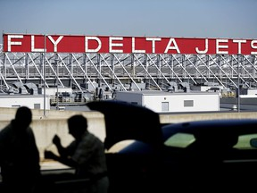 FILE - In this Thursday, Oct. 13, 2016, file photo, a Delta Air Lines sign overlooks the unloading area at Hartsfield-Jackson Atlanta International Airport, in Atlanta. On Thursday, Dec. 14, 2017, Delta announced it will order 100 Airbus A321neo jets with a sticker price of $12.7 billion and take an option to buy another 100 jets, a deal that Chicago-based Boeing had hoped to land.