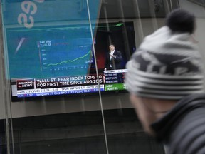 A pedestrian glances at a TV displaying financial news in Times Square, New York, Tuesday, Feb. 6, 2018. After big swings higher and lower, U.S. stocks are up slightly in afternoon trading Tuesday as investors look for calm after a global sell-off. The swings came one day after the steepest drop in 6 ½ years.