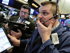 Traders at the New York Stock Exchange react to losses Thursday.